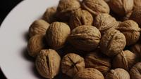Cinematic, rotating shot of walnuts in their shells on a white surface - WALNUTS 071