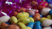 Rotating shot of colorful Easter candies on a bed of easter grass - EASTER 140