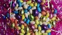 Rotating shot of colorful Easter candies on a bed of easter grass - EASTER 157