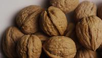 Filmische, roterende opname van walnoten in hun schaal op een wit oppervlak - WALNOTEN 053