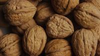 Filmische, roterende opname van walnoten in hun schelpen op een wit oppervlak - WALNOTEN 047