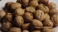 Filmische, roterende opname van walnoten in hun schaal op een wit oppervlak - WALNOTEN 070