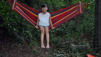 Liten tjej vilar liggande på hängmatta utomhus i slow motion