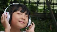 Kleines Mädchen hört Musik vom Kopfhörer und vom guten Gefühl