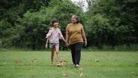Slow motion of Happy grandmother with granddaughter playing in the park