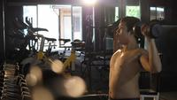 Young man hand holding dumbbell up exercises at gym fitness