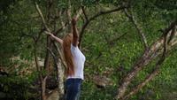 Hermosa mujer joven de pie con los brazos levantados disfrutar en la naturaleza