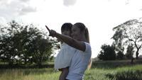Feliz madre e hija pasando tiempo juntos al aire libre, señalando con los dedos algo
