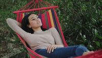 Mooie jonge vrouw die aan hangmat ligt te slapen en te ontspannen