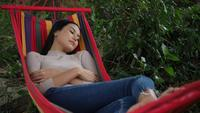 Beautiful young woman lying down to hammock sleeping and relax