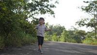 Happy asian little boy running on the street