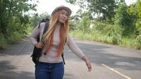 Reisenderfrauenwanderer, der auf der Straße und dem Gehen per Anhalter fährt.