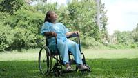 Femme âgée handicapée seule assis sur un fauteuil roulant seul dans le parc