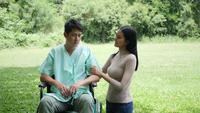 Handikappad ung man i rullstol med sin flickvän jubla i parken tillsammans
