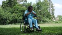 Ensam handikappad äldre kvinna sitter på rullstol ensam i parken