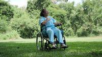 Einsame behinderte ältere Frau, die auf Rollstuhl allein im Park sitzt