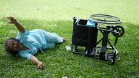 Paciente anciana que quiere ayudar después de una silla de ruedas volcada en el suelo.