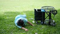 Älterer Frauenpatient möchte nach dem Rollstuhl helfen, der im Boden geworfen wird