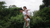 Vader die zijn dochter op zijn rug vervoert die ronddraait en in langzame motie glimlacht
