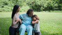 Grandmother sitting on wheelchair with daughter and granddaughter enjoy in the park together
