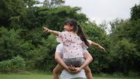Father carrying his daughter on his back spinning around and smiling in slow motion