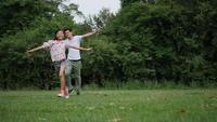 Slow motion, Vader en dochter lopen spelen genieten in het park