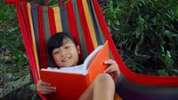 Liten flicka kyla på hängmatta och läsa en bokhistoria