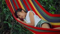 Långsam rörelse, liten tjej sover i hängmatta