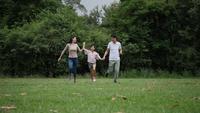 Cámara lenta de padres con hija corriendo disfrutando en el parque.