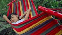 Au ralenti, petite fille dort dans un hamac