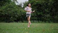 Slow motion, Glad liten tjej springande och ler i parken