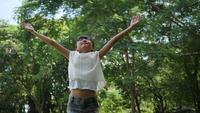 Het Aziatische meisje openlucht spelen in langzame motie, het Spinnen en het glimlachen en het opheffen dient de lucht in