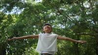 Asiatisches kleines Mädchen, das im Freien in der Zeitlupe spielt, spinnt und lächelt und Hände in der Luft anhebt