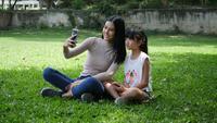 Unga mamma och lilla barns dotter ta en bild själv från smartphone eller mobiltelefon