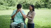 De gehandicapte jonge mens in een rolstoel met zijn meisje juicht samen in het park toe