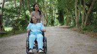 Older woman with her daughter pushing wheelchair around the park