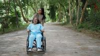Äldre kvinna med sin dotter som driver rullstol runt parken