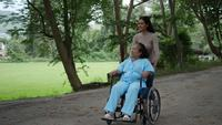 Mulher mais velha com a filha empurrando a cadeira de rodas ao redor do parque