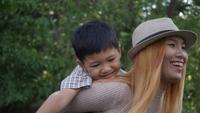 Aziatische jongen op een rit per paardrug met zijn moeder in langzame motie
