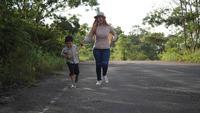 Cámara lenta, madre y su hijo corriendo en la calle.