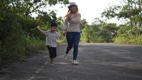 Slow motion, Mother and her son running in the street