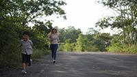 Zeitlupe, Mutter und ihr Sohn laufen auf die Straße