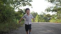 Gelukkige Aziatische kleine jongen die op de straat loopt