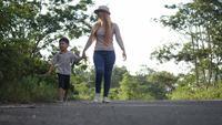 Slow motion, moeder en haar zoon wandelen in de straat