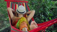 Junge Frau, die in der Hängematte mit Hutbedeckungsgesicht schläft