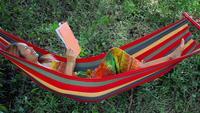 Junge Frau, die auf Hängematte niederlegt und ein Buch liest