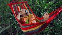 Young woman listening to music on a hammock.