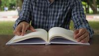 Cerrar hombre leyendo y abrir un libro en el parque