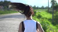 Zurück von der jungen schönen asiatischen Frau, die im Park rüttelt