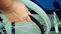 Close-up of a patient's hand holding a wheelchair and driving it alone.